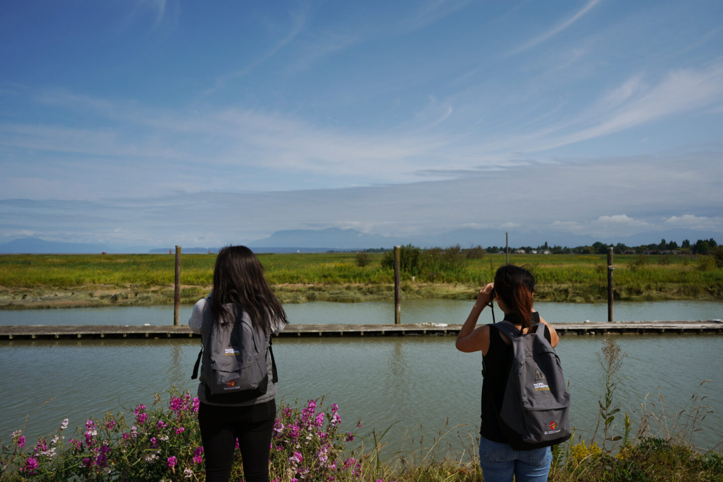 Two young birders looking out over the water with binoculars at Gary Point Park.